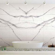 Book match Calacatta marble tiled wall in a designer white bathroom