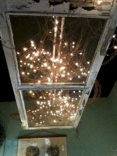 an old screen door hanging from a ceiling with lights
