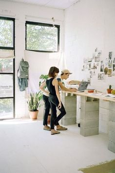 a large double stand desk built of cinder blocks and a wooden countertop for an industrial space