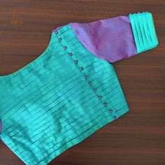 A classic, simplistic and beautiful design, this blouse is crafted with a layered pattern and cloth ball. Blouse Back Neck Designs, New Saree Blouse Designs, Simple Blouse Designs, Stylish Blouse Design, Sari Blouse, Blouse Neck Patterns, Saree Dress, Dress Designs, Kurta Neck Design