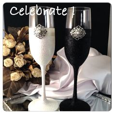 Bride and groom champagne flutes white ad black glitter and a matching ribbon with a rhinestone accent