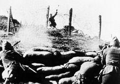 Un luchador insurgente lanza una granada de mano sobre una cerca de alambre de púas y soldados leales a con ametralladoras en Burgos, España, el 12 de septiembre de 1936.