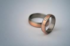 Snubní prsteny v kombinaci futuristického titanu a romantického zlata červené barvy. Vzájemnou kombinací těchto protikladů vzniká elegantní harmonický pár. Dámský prsten je osazen briliantem - titan, červené zlato - www.daloo.cz