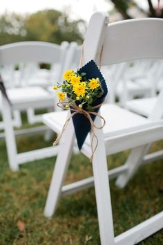 Yellow flowers in a small navy pouch on the back of a white wedding chair.