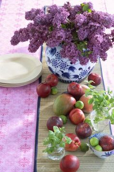 Fruits and flowers make an appealing mix along a straw runner. We used peaches, plums, mangoes, key limes and bunches of mint on either side of a lilac centerpiece. More spring centerpieces: http://www.midwestliving.com/homes/seasonal-decorating/50-bright-and-easy-spring-decorating-ideas/?page=26