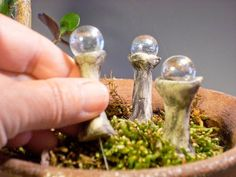 You could make them with golf tee and marbles. Fairy Garden Gazing Balls by laughingorangestudio on Etsy, $8.00. Y