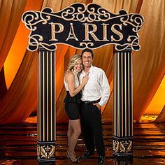 Our Paris Arch is made of sturdy cardboard and features a black and gold sign that says Paris.