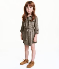 Khaki green/hearts. Shirt dress in soft woven fabric with a printed pattern. Collar, concealed buttons at front, and attached tie belt at waist. Chest