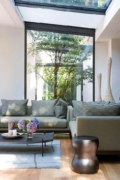 Lounge that sits with windows to a courtyard and skylight above.