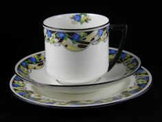 Doulton deco: unnamed tea trio by Robert Allen, H1682, RA9759, c1923 (pattern). Yellow/blue colourway - geometric yellow and blue flower detail with motif to inner cup rim and black and yellow highlights and black trim. Variant of unnamed Robert Allen pattern (H1651).