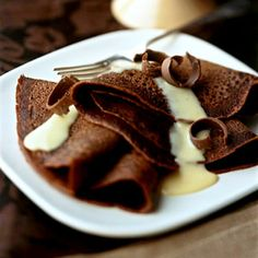CHOCOLATE CREPES WITH NUTMEG VANILLA SAUCE~ 1 cup all-purpose flour, 1/3 cup sugar, 1/3 cup unsweetened cocoa powder, 2 eggs lightly beaten, 1 cup milk, 2 tbsp butter melted, 1 tsp vanilla, ½ cup whipping cream, 2 tbsp sugar, Nutmeg Vanilla Sauce, chocolate curls.