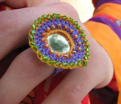 this handmade ring is completely crocheted. The little mirror surrounded of beads makes it to an eye-catcher.