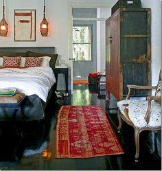 black gloss painted floors, Asian antique armoire, vintage lanterns, cranberry rug..