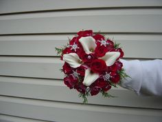 Winter wedding:  Red and white bouquet of red roses and white calla lilies with a touch of winter greens.  The rhinestone snowflakes are the perfect touch!  Designed by Whimsical Welcomes Floral Designs