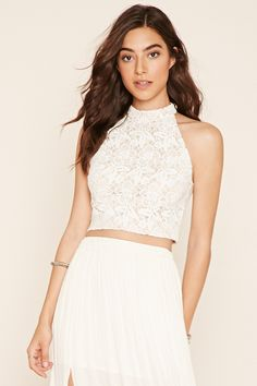 A sleeveless crop top featuring allover floral crochet lace, a high neckline, and an exposed back zipper.