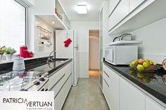 Cozinha reformada com revestimento meia parede com iluminação sobreposta.