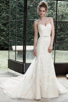 Winstyn Dreamy lace and tulle combine to create this elegant fit and flare wedding dress, accented with timeless sweetheart neckline. A glittering Swarovski crystal motif on an optional grosgrain ribbon belt adds a touch of drama. Finished with...