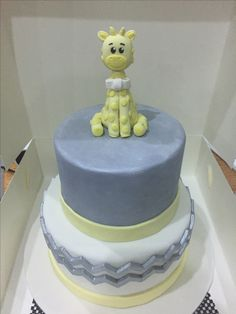 Baby shower cake with giraffe topper. Yellow white and silver