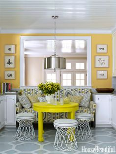 Bright yellow walls — Benjamin Moore's Inner Glow — and an even brighter citron table from HB Home brought the white-and-gray kitchen in a Charlotte, North Carolina, house to life. Designer Lindsey Coral Harper turned wire side tables from ABC Carpet & Home into stools. Dark brown floors were transformed with a large geometric pattern, painted by Jay C. Lohmann. Pendant light from Robert Abbey. Hugo Guinness prints from John Derian.   - HouseBeautiful.com