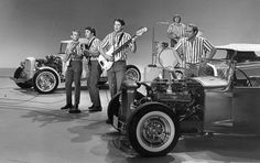 Beach Boys members Al Jardine, Carl Wilson, Brian Wilson, Dennis Wilson, and Mike Love rock out amid hot rods on The Ed Sullivan Show in 1964.