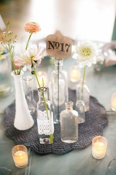 Mixed bottles centerpiece, table numbers out the top of bottle