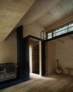 Vertical lengths of timber clad the walls of this hut, while metal sheeting covers its mono-pitched roof and chimney.