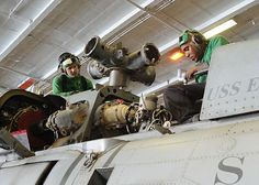 Aviation Machinist's Mate 2nd Class Thomas S. Upp cleans and inspects parts while Aviation Machinist's Mate 2nd Class Ernest Hall torques the main gear box mount feet bolts on an aircraft aboard USS Enterprise (CVN 65).