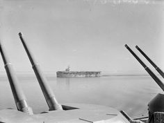 HMS Emperor steams slowly over the Bitter Lakes entry to the Suez Canal en route to Trincomalee, Ceylon in February of 1945 to join the 21st Aircraft Carrier Squadron of the Eastern Fleet. She is seen here beautifully framed by two twin 4.5 pound gun turrets on HMS Indomitable, a Royal Navy Illustrious Class fleet carrier. The 21st Aircraft Carrier Squadron would include His Majesty's escort carriers Emperor, Begum, Empress, Shah, Ameer, Khedive, Slinger and Speaker. Photo: Imperial War…