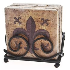 Add some majesty to your beverage service with this tavertine stone coaster set. The coasters feature an intricate fleur-de-lis design and are housed in a beautiful steel holder. Cork backing provides a non-slip surface for these durable stone coasters.