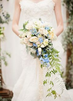 How incredible is this cascading bouquet filled with ivory floral, lush greens, and a magical touch of blue!