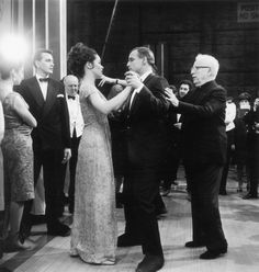 Marlon dancing with Charlie Chaplin's daughter while he looks on.