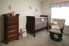 Simple, yet elegant kids room displaying a traditional sense with a dark brown crib, rocking chair and wood furniture throughout. While there is certainly a pink vibe in the entire room, we imagine the homeowner went with a neutral choice for the window valance adding in some blue.
