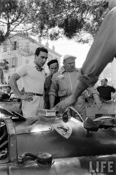 Eugenio Castellotti standing over his Lancia/ Ferrari D50 at the Monaco Grand Prix race, May 1956.