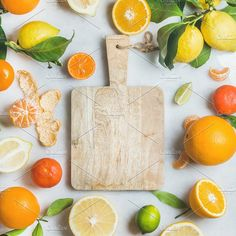 #Variety of fresh citrus fruit  Variety of fresh citrus fruit for making juice or smoothie and wooden chopping board over light grey marble background top view copy space square crop. Healthy eating vitamin clean eating concept