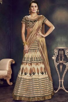 Enchant everyone around in this riveting beige color designer lehenga choli. This beautiful art silk fabric party wear 3 piece lehenga choli is strikingly decorated with embroidery, zari work and thread work combined with attractive borders which are the Brocade Lehenga, Lehenga Style Saree, Raw Silk Lehenga, Lehenga Choli Online, Sarees Online, Blouse Online, Bridal Lehenga, Bollywood Designer Sarees, Latest Designer Sarees