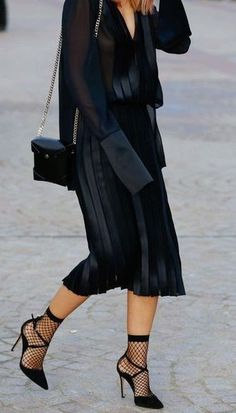 all black. street style. pleated skirt. fishnet socks. heels. sheer blouse.