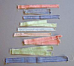 Vävda band i bomull, Leksand, Dalarna, Sverige. Banden, i olika färger, mönster och bredder är vävda i rips. Varp och inslag i kulört och oblekt bomullsgarn.