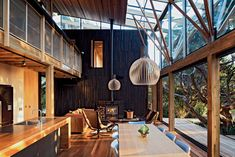 Herbst Architects' Under Pohutukawa in Piha, New Zealand is a modest beach cottage constructed from timber and corrugated iron.