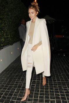Gigi Hadid in white distressed denim, a polished cape, and a messy topknot