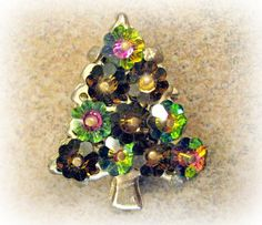 Vintage Christmas Tree Pin Margarita Rhinestone Brooch A bit different from your traditional Christmas Tree brooch, and a great addition to a collection. Margarita rhinestones in vitrail medium and topaz are arranged in a tree shape with lots of sparkle. Gold tone metal. Pin is 1.5 inches tall and 1.25 inches wide. Margarita stones are just 3/8 inch across.  See the rest of my shop here: https://www.etsy.com/shop/SentimentalVintager