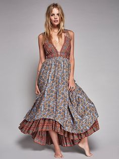 Rhythm of Love Dress   Printed flowy maxi dress featuring a plunging neckline with crisscross strap detailing with metal accents. Elastic band at the waist for an easy fit with an adjustable belt. Lined.