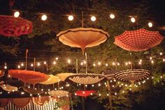 Umbrellas double as whimsical wedding decor hanging from cafe lights.