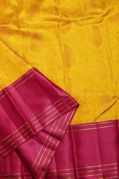 This vivid yellow sari is a kanchivaram silk with a beautiful floral pattern all over in yellow and canary yellow thread work. The border is in magenta with a satin finish and gold zari stripes. Th…
