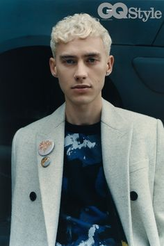 Olly Alexander wears a black and blue crew neck sweater, a black and yellow techno kit body warmer, a greige worsted wool long coat and a selection of badges, all by Dior Homme