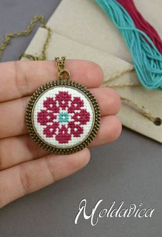 Round pendant with traditionally embroidered flower symbol. The cross stitch neck . - Round pendant with traditionally embroidered flower symbol. The cross stitch neck … - Tiny Cross Stitch, Cross Stitch Boards, Cross Stitch Alphabet, Modern Cross Stitch, Cross Stitch Flowers, Cross Stitch Designs, Cross Stitch Patterns, Cross Stitching, Cross Stitch Embroidery