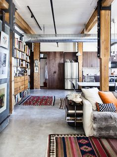 Rustic industrial interior. Big beams, rough wood, concrete floors, and modern appliance and furnishings.