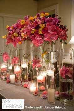 Gorgeous floating candle centerpiece covered in Orchids, Roses, and Ranunculus. Very whimsical and fantastic. #weddingreception @janaeshields