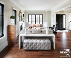 living room, parisian chic, plinth, topiary, english sofa, sheepskin pillows, zebra print pillows, glass coffee table, black arm chairs, walnut floors, tufted bench, console table