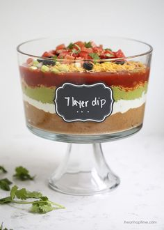 7 layer dip recipe -layers of salsa, guacamole, sour cream, beans, cheese, pico de gallo and olives. The perfect appetizer for game day or a friends gathering. People will gather around until it's gone!