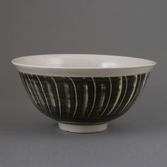 DAVID LEACH, porcelain bowl, pale celadon glaze the exterior with blue glaze an alternating incised and combed vertical lines, impressed DL seal, H 10.3 cm., D 21 cm